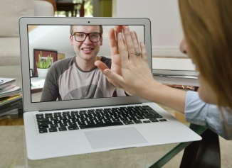 Couple touching hands over Skype.